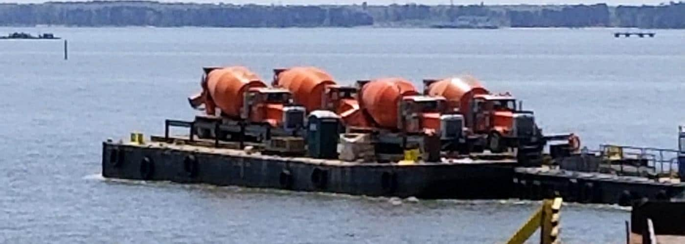 4 concrete trucks on a barge
